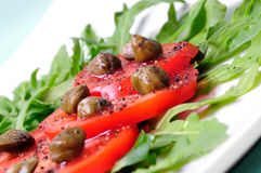 Salad with fresh tomatoes, capers . arugula Royalty Free Stock Photos