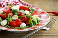 Salad with fresh tomatoes and quail eggs. Salad with fresh tomatoes, arugula and quail eggs stock image