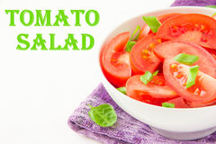 Salad from fresh tomatoes, spring green onions and black pepper. Isolated salad with fresh tomatoes, spring green onions and black pepper on purple towel Stock Photos