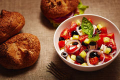 Salad with fresh vegetables and burger and buns in the back. stock photography