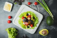 Salad with fresh vegetables, cheese, olives and basil on grey table. Tasty food background. Flat lay royalty free stock image