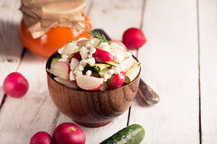 Salad with fresh vegetables and cottage cheese. Horizontal orientation. Wooden table. Salad with cucumber, radish, cottage cheese, spinach, olive oil and dill Stock Photo