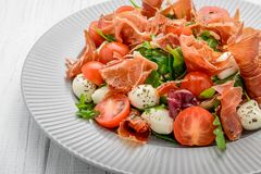 Salad with fresh vegetables with dried tomatoes, meat and mustard, mozzarella, prosciutto stock photos