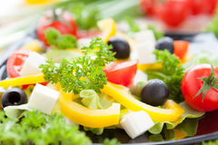 Salad with fresh vegetables and feta on a black plate Stock Image