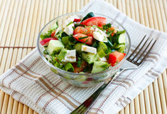 Salad with fresh vegetables and feta cheese. In a salad bowl on a fabric napkin Stock Photos