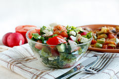 Salad with fresh vegetables and feta cheese. In a salad bowl on a fabric napkin. Roasted vegetables and salad ingredients in the background Stock Photography