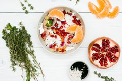 Salad with fresh vegetables, feta cheese, garnets and tangerines. healthy diet or vegetarian food on a wooden background. Top view Stock Images