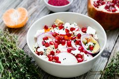 Salad with fresh vegetables, feta cheese, garnets and tangerines. healthy diet or vegetarian food on a wooden background. Top view Royalty Free Stock Photos
