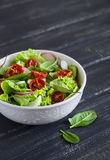 Salad with fresh vegetables, garden herbs and sun-dried tomatoes in a white bowl Stock Image