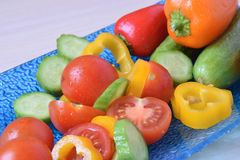A blue glass plate with bright multicolor vegetables. Salad with fresh vegetables. Green cucumbers, red, orange and yellow peppers and red cherry tomtoes Royalty Free Stock Images