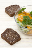 Salad with fresh vegetables and greens, whole wheat bread on a light makisu Stock Photography