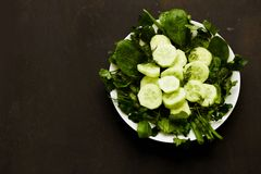 Salad with fresh vegetables, herbs, and cucumbers royalty free stock photography