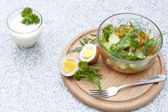 Salad with fresh vegetables and herbs in a glass bowl on a wooden board, boiled eggs and yogur. T with herbs royalty free stock photo