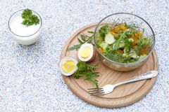 Salad with fresh vegetables and herbs in a glass bowl on a wooden board, boiled eggs and yogur. T with herbs stock images