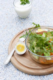 Salad with fresh vegetables and herbs in a glass bowl on a wooden board, boiled eggs and yogur. T with herbs stock photos