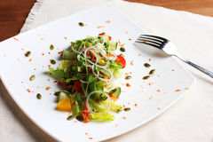Salad with fresh vegetables, pumpkin seeds, oranges on white plate. With fork and napkin stock photography