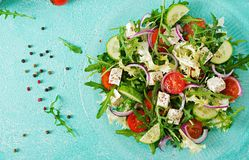 Salad of fresh vegetables - tomato, cucumber and feta cheese in Greek style. Flat lay. Top view Stock Photos