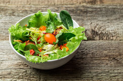 Salad with fresh vegetables - tomatoes, carrots, bell peppers and mixed greens - arugula, mesclun, mache. Royalty Free Stock Photography