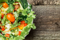 Salad with fresh vegetables - tomatoes, carrots, bell peppers and mixed greens - arugula, mesclun, mache. Royalty Free Stock Images