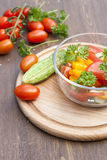 Salad of fresh yellow and pink tomatoes and cucumber with parsley in a glass bowl. On a wooden table royalty free stock image