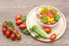 Salad of fresh yellow and pink tomatoes and cucumber with parsley in a glass bowl. On a wooden table stock photography