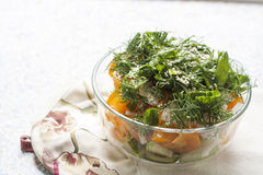 Salad of fresh yellow tomatoes and cucumber with herbs and sesame seeds. In a glass bowl on a table royalty free stock photography