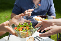 Salad on garden party. Host serving healthy fresh salad on garden party Royalty Free Stock Photos