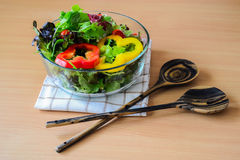 Salad in glass bowl. With wooden spoon and fork Royalty Free Stock Photo