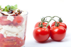 Salad in glass with tomatoes, feta cheese and fresh basil Royalty Free Stock Image
