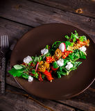 Salad with goat cheese,greens and grilled pepper on brown plate. Royalty Free Stock Photo