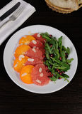 Salad of grapefruit, persimmon, pomegranate and rocket salad Royalty Free Stock Images