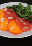 Salad of grapefruit, persimmon, pomegranate and rocket salad Stock Photo