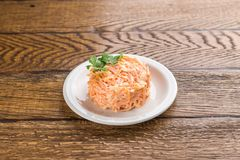 Salad with grated carrot and sour cream isolated on wooden background. Side view stock images