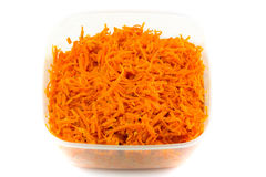 Salad of grated carrots in plastic container isolated on white Royalty Free Stock Image