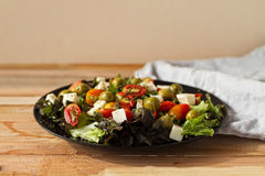 Salad Greek, salad ovoshny, tomatoes, olives, cheese, healthy food, a diet with salad, very appetizing salad on a wooden table. Stock Photo