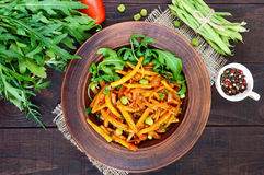 Salad from green beans, stewed with onions in tomato sauce and green leaves of arugula Stock Image
