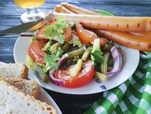 Salad green beans, tomato, fried beef onions sausages snack traditional appetizer beer on a wooden background barbecue plate stock photography