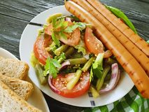Salad green beans, tomato, fried sausages on a wooden background, bread red pepper stock photo