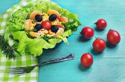 Salad green leaf lettuce. Corn kernels, mandarin slices, grated cheese, cherry tomatoes, a sprig of rosemary, cloth napkins, black olives on a wooden light Royalty Free Stock Photos