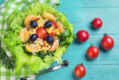 Salad green leaf lettuce. Corn kernels, mandarin slices, grated cheese, cherry tomatoes, a sprig of rosemary, cloth napkins, black olives on a wooden light Stock Images