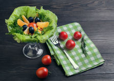 Salad green leaf lettuce. Corn kernels, mandarin slices, grated cheese, cherry tomatoes, a sprig of rosemary, cloth napkins, black olives on a wooden light Stock Image