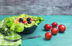 Salad green leaf lettuce. Corn kernels, mandarin slices, grated cheese, cherry tomatoes, a sprig of rosemary, cloth napkins, black olives on a wooden light Stock Photo