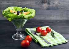 Salad green leaf lettuce. Corn kernels, mandarin slices, grated cheese, cherry tomatoes, a sprig of rosemary, cloth napkins, black olives on a wooden dark Stock Photography