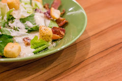 Salad. On green plate on wooden table Royalty Free Stock Photography