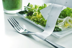 Salad, green smoothie and measuring tape Royalty Free Stock Images