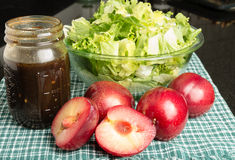 Salad greens and fresh plums Stock Image