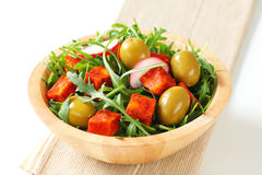 Salad greens with olives and spicy cheese. Salad greens with  green olives and diced paprika-coated cheese Stock Image
