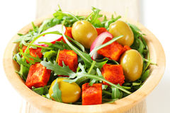 Salad greens with olives and spicy cheese. Salad greens with  green olives and diced paprika-coated cheese Royalty Free Stock Photo