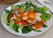 Salad greens with persimmon and almonds Stock Photo