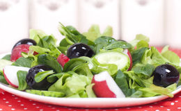 Salad with greens, radishes, black olives and olive oil. Spring salad with greens, radishes, black olives and olive oil on a white plate Stock Photo
